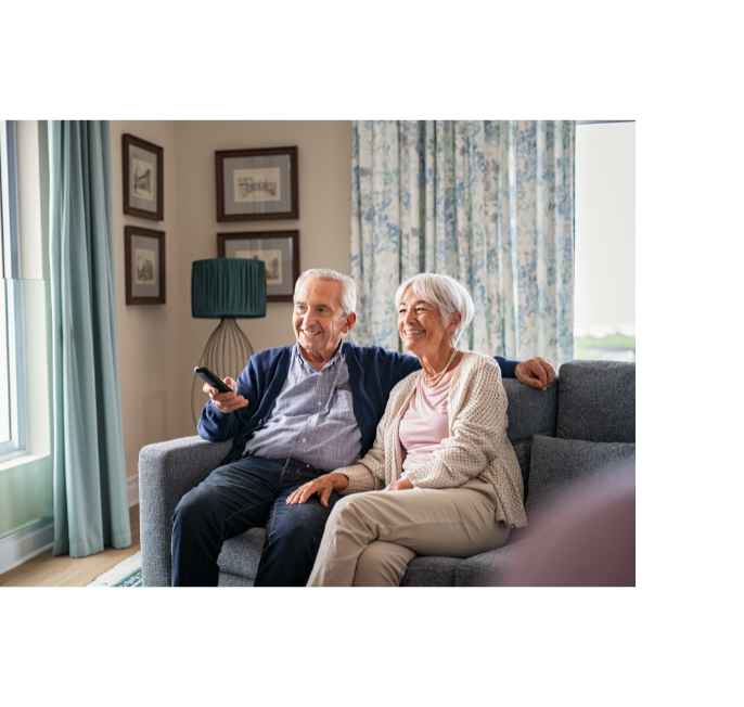 old couple watching tv at home